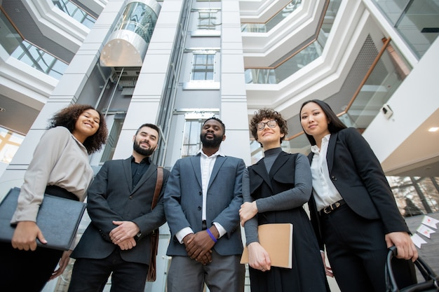 半円形のオフィスホールに立つフォーマルな服装のビジネススペシャリストのグループ