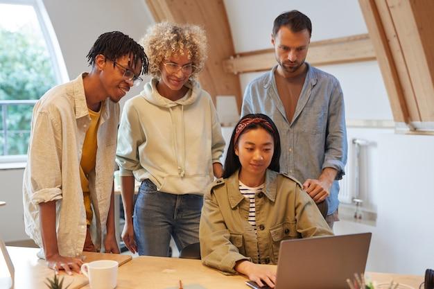 彼の同僚がチームで働いていることを彼らに示しているラップトップでのプレゼンテーションを見ているビジネスチームのグループ