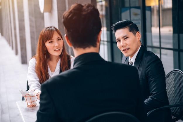 ビジネス地区のコーヒーショップでパートナーと新しいビジネスプロジェクトとマーケティング計画について話している実業家と実業家のグループ