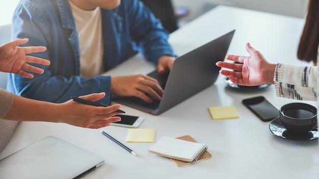 Группа бизнесмена вместе обсуждая и работая над портативным компьютером в офисе