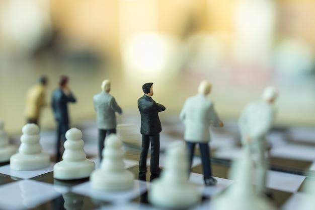 チェスの駒でチェス盤に立っているビジネスマンのミニチュアフィギュアの人々のグループ