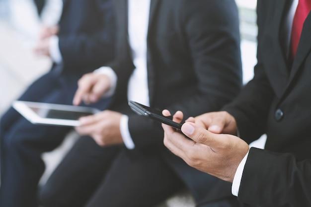 ビジネスマンの人々3のグループは、モバイルスマートフォンやコンピューターのタブレットを見て自分の画面を見て座っています。テクノロジーデジタルガジェットを使用する。