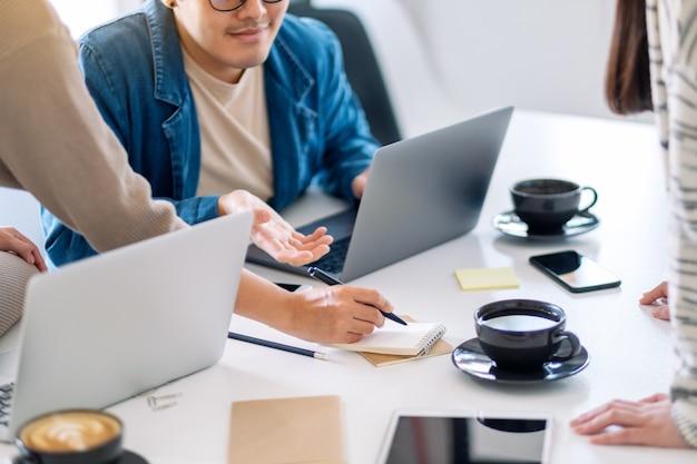 Группа бизнесмена, использующего портативный компьютер во время обсуждения и записи на ноутбуке на столе в офисе