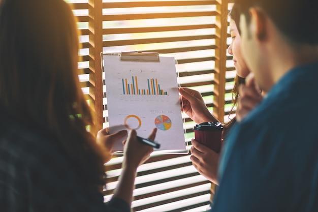 Группа бизнесменов, работающих и обсуждающих бизнес-данные вместе в офисе