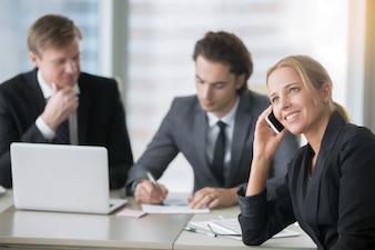 コンピューターと近代的なオフィスの机でビジネスマンのグループ
