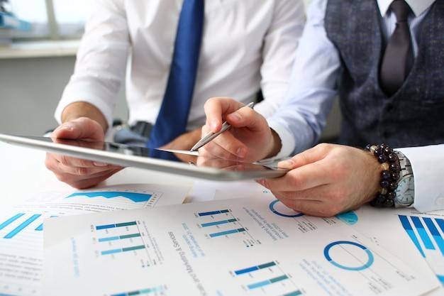 Группа бизнесменов указывает пальцем и серебряной ручкой в руках