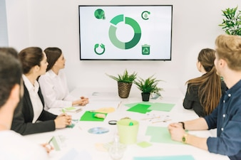 Group of businesspeople looking at natural resources icon in meeting