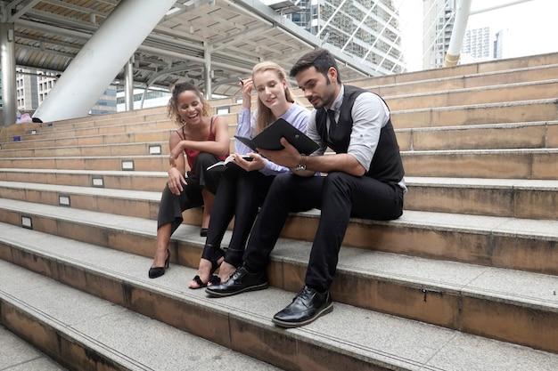 Группа бизнесменов, использующих цифровой планшет вместе перед окнами офисного здания с видом на город