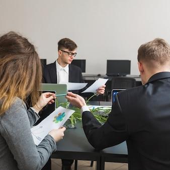 Группа бизнесменов, работающих на графике в офисе