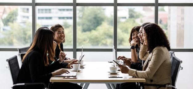 Группа деловых женщин в официальной деловой одежде, улыбаясь, сидя вместе за столом для совещаний, набирая текст на портативном компьютере и сенсорном планшете, беседует в конференц-зале возле стеклянных окон.
