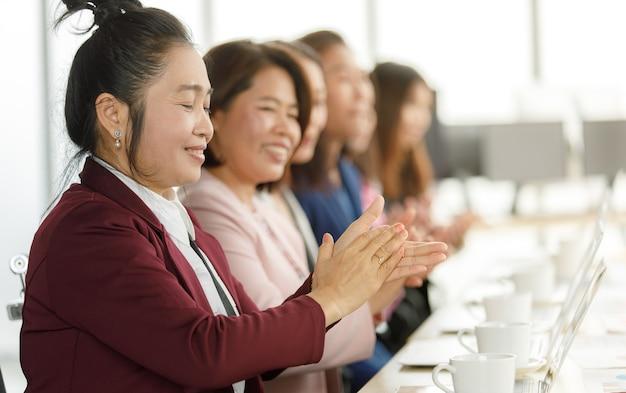 Группа деловых женщин в костюме сидит за рабочим столом и хлопает в ладоши, чтобы поблагодарить кого-то в современной офисной компании. концепция хороших обстоятельств в компании с друзьями и коллегами.