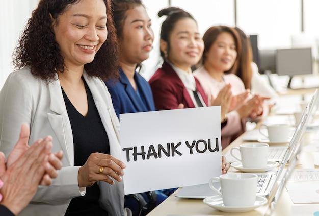 Группа деловых женщин сидит за рабочим столом, хлопает в ладоши и показывает слово благодарности за благодарность кому-то в современной офисной компании. понятие о хороших обстоятельствах в компании с коллегами.