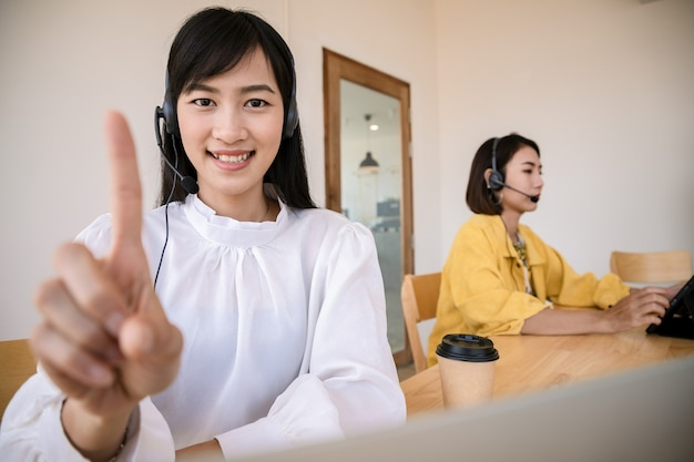 콜센터 직원 그룹이 헤드폰과 마이크 케이블을 통해 고객에게 이야기하고 서비스를 제공합니다. 말하기, 기억력 및 정보 기록 기술을 갖춘 전문가. 터치 스크린