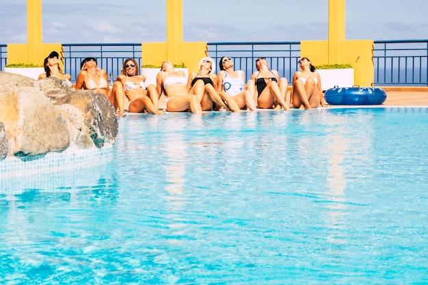 白人の若い女性の友人のグループは、夏の間にプールで日光浴を楽しんでいます