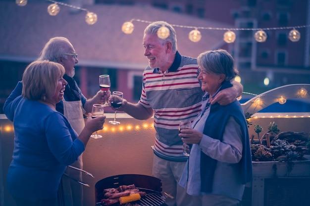 陽気で幸せな先輩の友人のグループは、街の景色を望む自宅のテラスで屋外で夕食をチリンと楽しんでいます