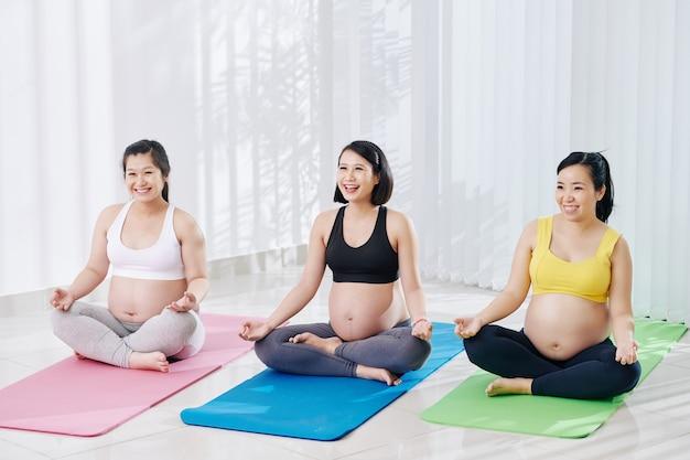 Группа веселых азиатских беременных женщин, практикующих йогу в оздоровительном клубе