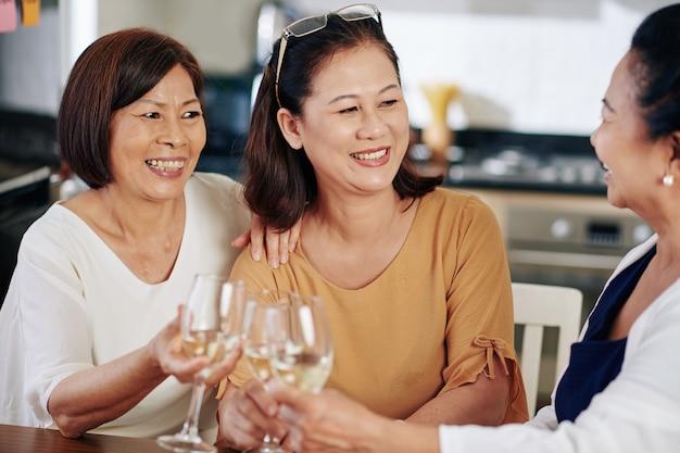 식탁에서 화이트 와인을 마시고 건강과 가족 문제에 대해 이야기하는 쾌활한 아시아 노인 여성 그룹
