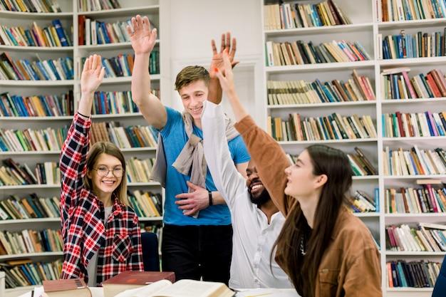 手を上げて教育の成功を示すカジュアルな服装で陽気な4つの多民族の学生のグループ
