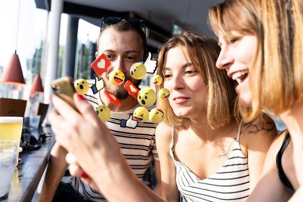 電話の画面と電話からのいくつかの写真を見て陽気な友人のグループ