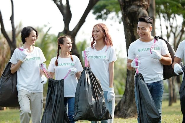 Группа веселых друзей волонтеров в местном парке и уборка мусора на земле