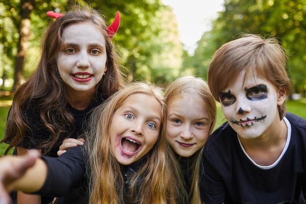 屋外で自分撮り写真を撮っている間、ハロウィーンの衣装とフェイスペイントで陽気な子供たちのグループ
