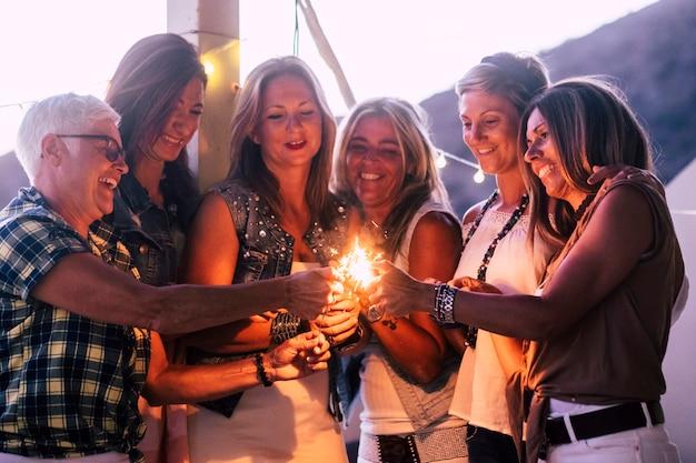 友情のある陽気な混合年齢の女性のグループは、家のテラスで線香花火を使用して新年の夜を祝い、笑いながらライフスタイルを楽しんでいます