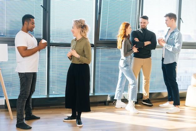 창가와 밝은 햇빛을 배경으로 직장에서 커피를 마시는 쾌활한 다민족 동료들. 젊은 비즈니스 팀은 현대적인 사무실에서 함께 채팅하고 토론합니다.