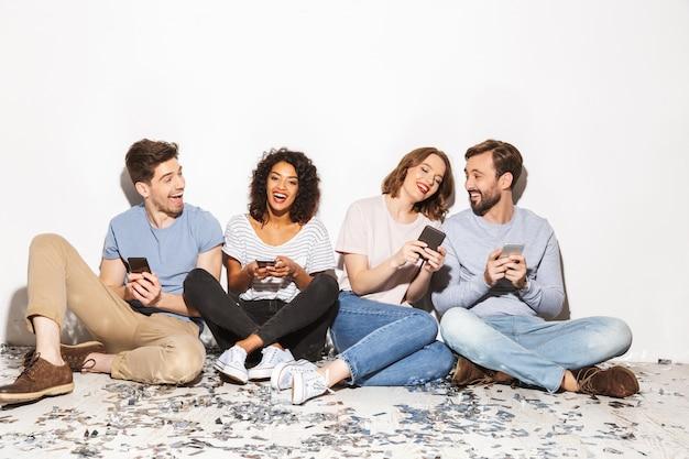 Группа веселых многорасовых людей, сидящих на полу