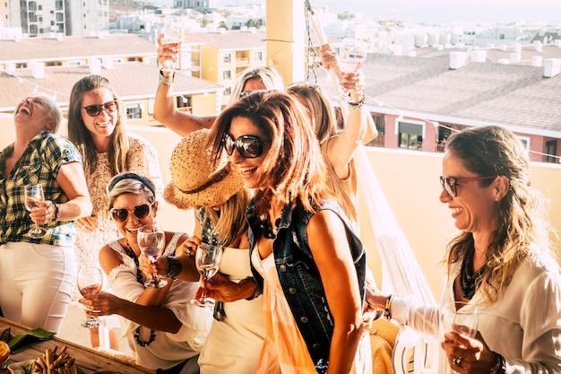 陽気な人々のグループは、若い女性と年配の女性が一緒にワインを祝い、街の景色を望む屋外テラスで楽しんでいます