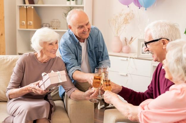 Группа веселых старших друзей, чокающихся шампанским во время приготовления тостов