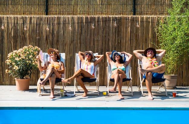 야외 뒤뜰에 있는 수영장 옆에 앉아 휴식을 취하는 쾌활한 노인들.