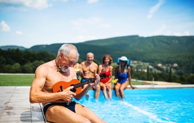 파티 컨셉인 뒤뜰에 있는 야외 수영장에서 기타를 든 쾌활한 노인들.