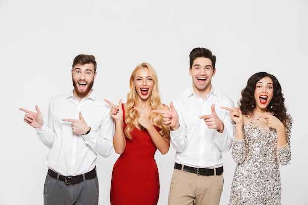 Группа веселых, умных одетых друзей, стоящих изолированно над белой, празднуя новый год, указывая пальцами в сторону