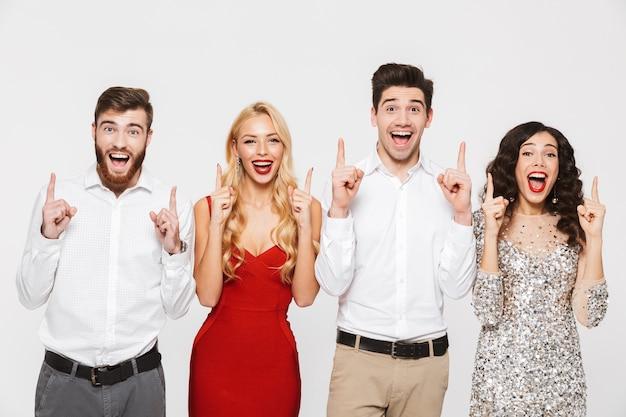 Группа веселых, умных одетых друзей, стоящих изолированно на белом, празднует новый год, указывая пальцами вверх