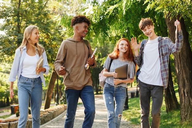 キャンパスを歩いている陽気な学生のグループ