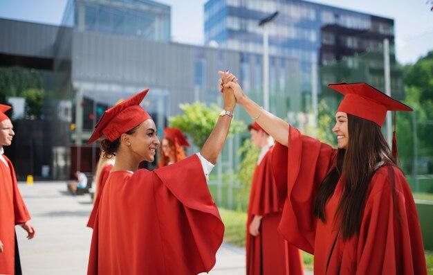 야외에서 축하하는 쾌활한 대학생 그룹, 졸업 개념.