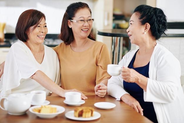 쿠키와 함께 차를 마시고 뉴스와 가십에 대해 토론하는 쾌활한 베트남 여성 그룹
