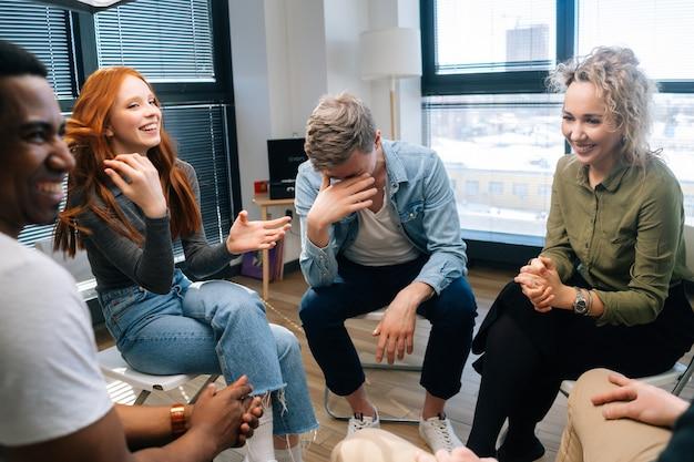 쾌활한 젊은 활동의 그룹 다양한 다민족 동료들이 창 근처에서 브레인스토밍하는 동안 웃고 있습니다. 팀워크에서 함께 일하는 행복한 창의적인 동료들은 사무실에서 프로젝트 계획을 논의합니다.