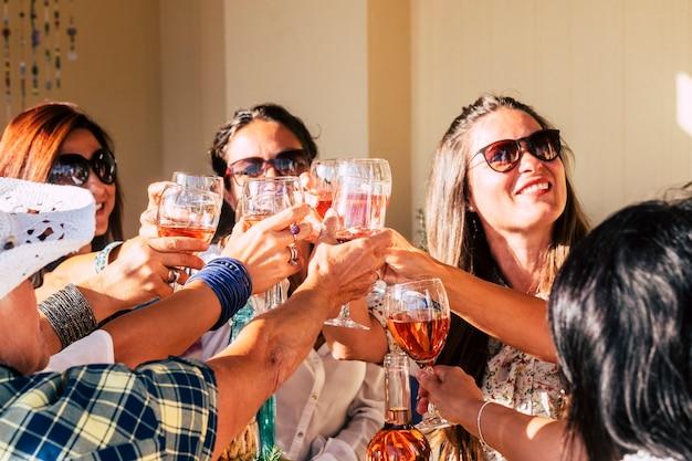 一緒に赤ワイングラスをチリンと鳴らして楽しんで祝う陽気な若い白人女性のグループ