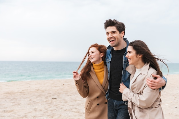 Группа веселых молодых друзей, гуляющих на берегу моря, обнимающихся