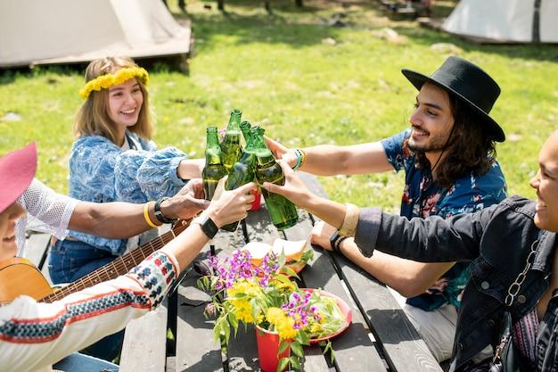Группа веселых молодых многонациональных друзей, сидящих за столом на открытом воздухе и тостов с бутылками в кемпинге