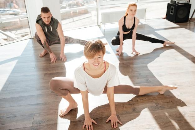 Группа веселых молодых людей, практикующих йогу с тренером