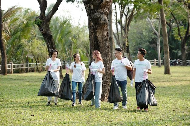 캠퍼스나 도시 공원에서 고른 쓰레기 봉투를 들고 있는 쾌활한 젊은 자원 봉사자 그룹