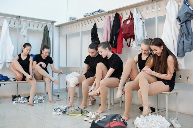 ロッカールームのベンチに座って、足にバレエシューズを置くチアリーディングの女の子のグループ