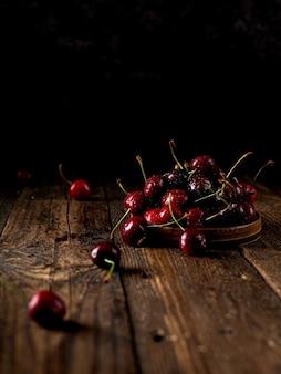 어두운 나무 배경이나 테이블에 있는 체리 그룹 또는 테이블 즙이 많은 신선한 체리 베리