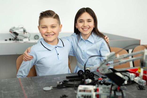 子供たちのグループは、プラスチック部品から組み立てられたロボットで遊んでいます。 Premium写真