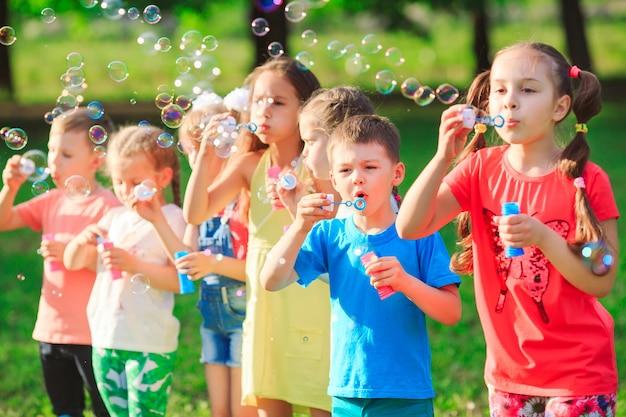 Группа детей дует мыльные пузыри