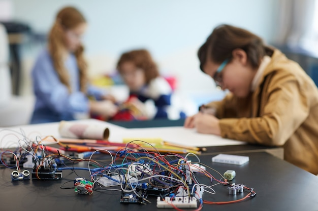 学校の工学の授業でロボットを作る子供たちのグループ、前景のワイヤーと電気回路、コピースペースに焦点を当てる