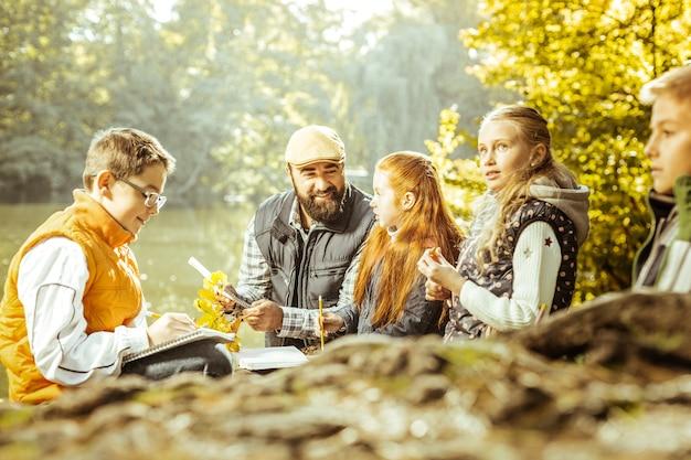 天気の良い日に森でレッスンをしている子供たちのグループ