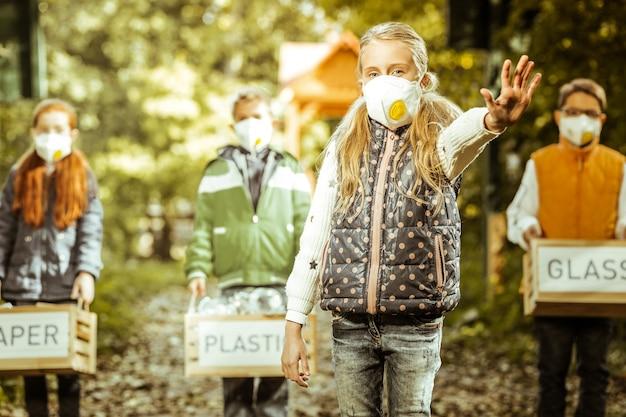 良い日に地球保護への意識を高める仕分けされたゴミ箱を持っている子供たちのグループ